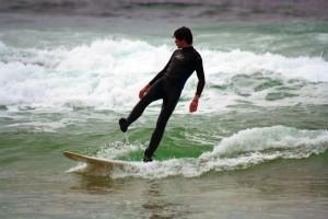 Surfer auf schwieriger Welle – Achtsam sein
